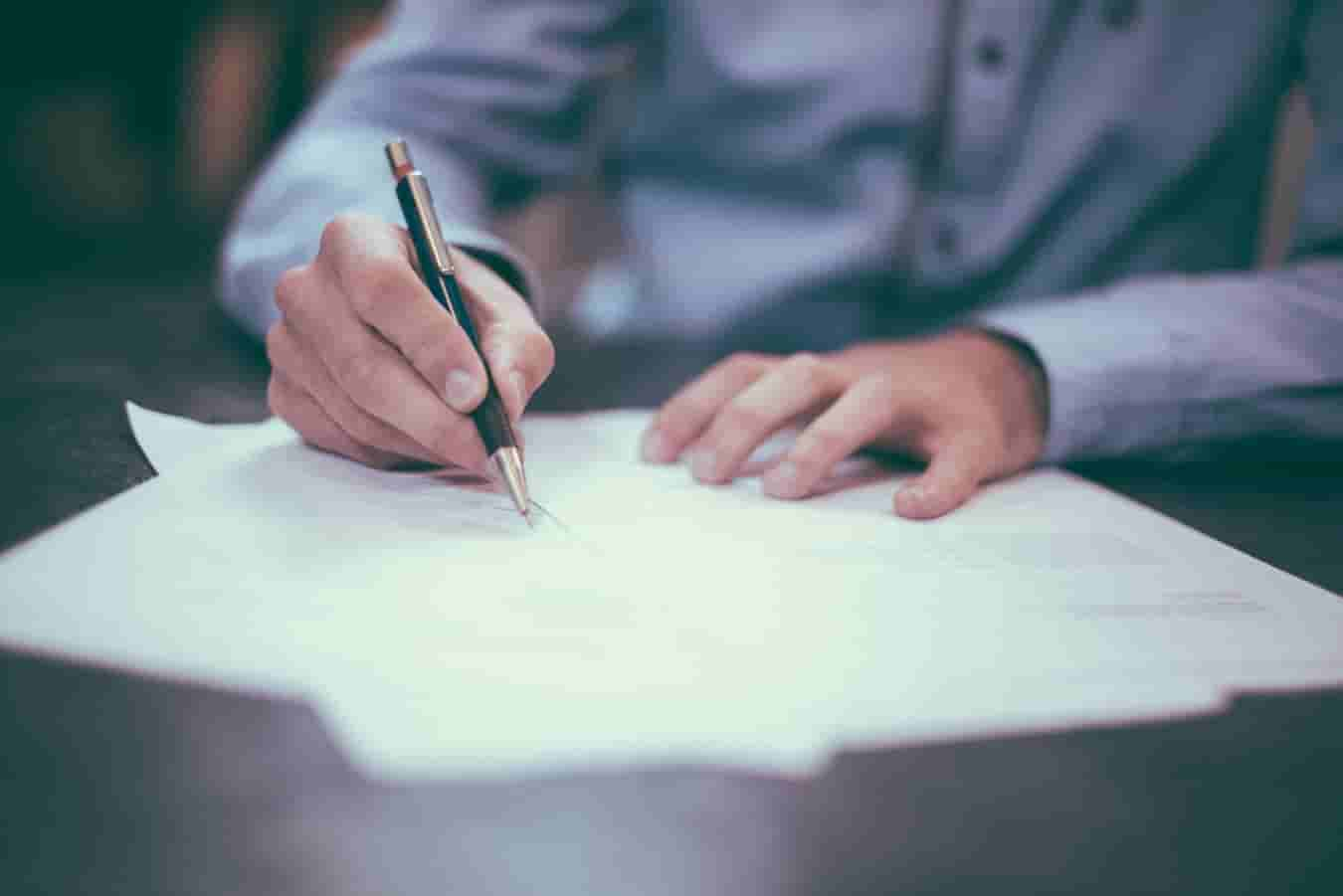 Image | person sitting at desk signing papers